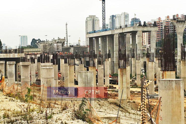 Ao fundo, dezenas de funcionários constroem a estação Jardim Aeroporto enquanto material chega para a obra do pátio